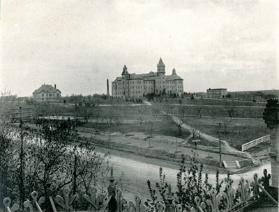 Old Main 1899: Photography of Victorian Gothic styled building in the far distance surrounded by large expanse of grass.  Two significantly smaller buildings are to the right and left of Old Main in the center of the photograph.