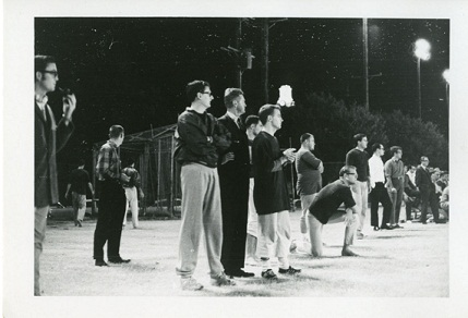 Approximately 12 male students standing next to each other on the sidelines of the field, looking to their left with arms crossed.