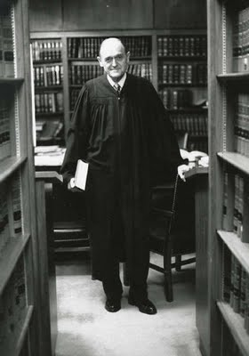 Judge Justice in Chambers: an elderly, bald man, smiling and wearing black robes standing in front of a table with bookshelves behind him.
