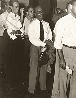 Heman Sweatt, an African American man, standing in line among white men waiting to register for classes.